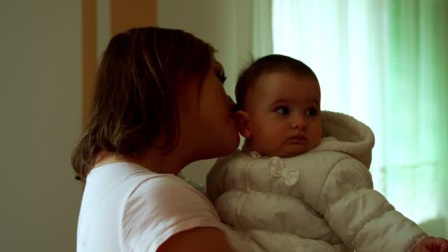 vidéos et rushes de une femme retenant une petite fille et grignotant son oreille - tante