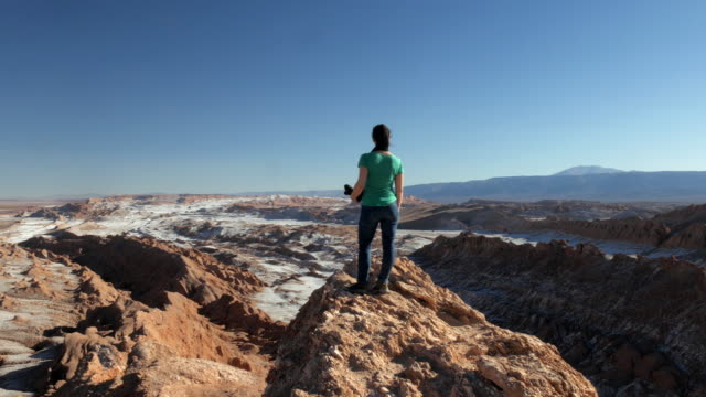 woman holding a camera and looking at the desert landscape - san pedro de atacama stock videos & royalty-free footage