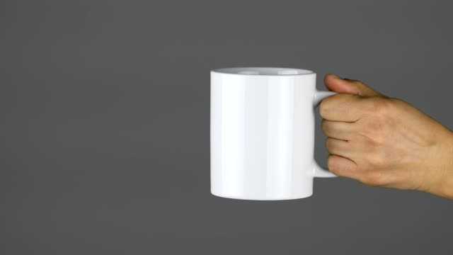 vídeos de stock e filmes b-roll de woman holding a ceramic cup, relaxing, blank, gray background, breakfast, cafe - caneca