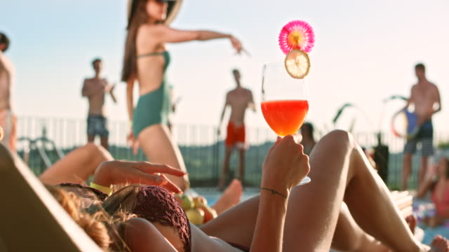 slo mo woman holding a cocktail lying on the deckchair by the pool while her friends are dancing by the pool - deckchair stock videos & royalty-free footage