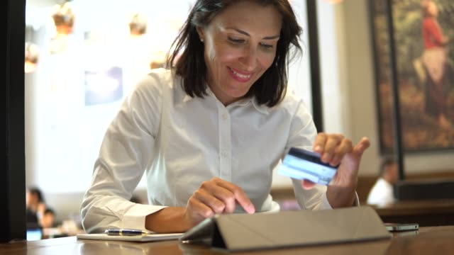 woman holding a credit card and buying online with a digital tablet  in cafe - paying online stock videos & royalty-free footage