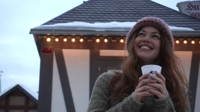 Woman holding a cup in front of food stand