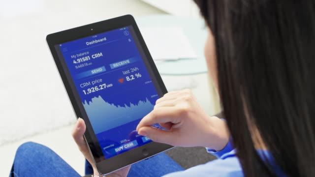 vídeos de stock, filmes e b-roll de mulher segurando um tablet digital e envio de cryptocurrency - send