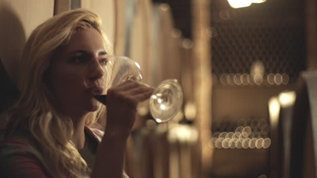 woman holding a glass of red wine and tasting it - winemaking stock videos & royalty-free footage