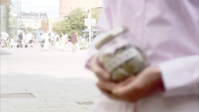 woman holding a jar full of money, sweden. - only mid adult women stock videos & royalty-free footage