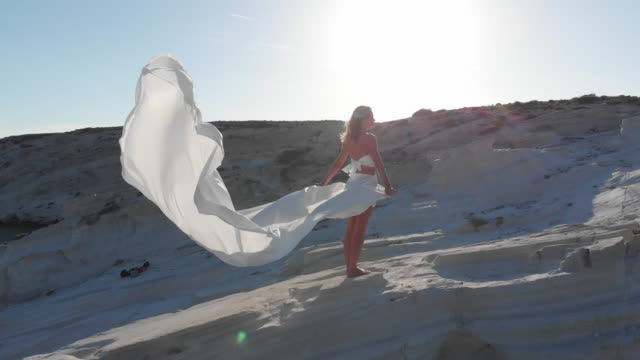Woman Holding a Large, White Fabric in Seaside on a Rock, an Aegean Coast