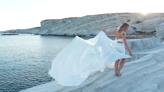 frau hält ein großer, weißer stoff im meer auf einem felsen in ägäische küste - griechenland stock-videos und b-roll-filmmaterial