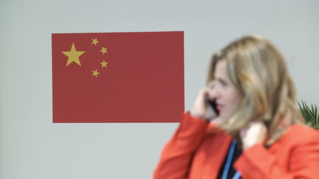 a woman holding a mobile phone walks past a chinese flag at the china pavilion at the unfccc cop25 climate conference on december 3 2019 in madrid... - fifa world cup 2010 stock videos & royalty-free footage