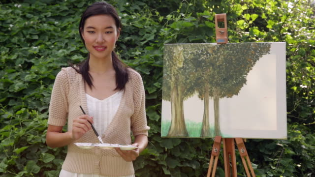 ms woman holding a paintbrush standing in front of a painting. - 画家点の映像素材/bロール