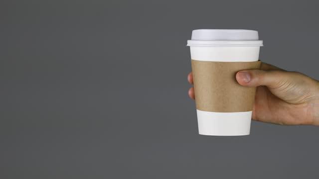 vídeos de stock e filmes b-roll de woman holding a paper cup on gray background. - copo descartável