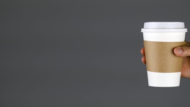 kvinna som håller en pappers mugg, avslappnande, blank, grå bakgrund, frukost, café - engångsmugg bildbanksvideor och videomaterial från bakom kulisserna