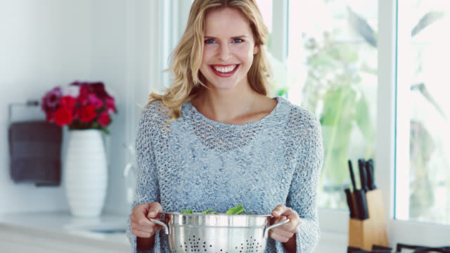 a woman holding a salad colander and smiling to camera - urbanlip stock videos & royalty-free footage