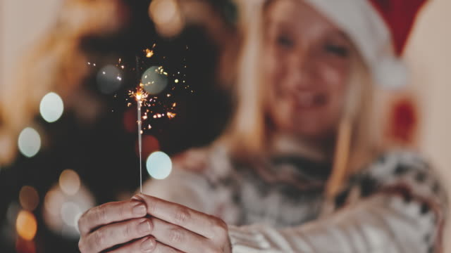 slo mo woman holding a sparkler for christmas - 40 seconds or greater stock videos & royalty-free footage