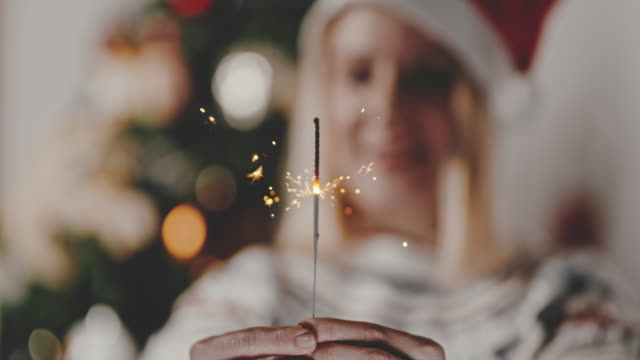 slo mo woman holding a sparkler on new year's eve - advent stock videos & royalty-free footage