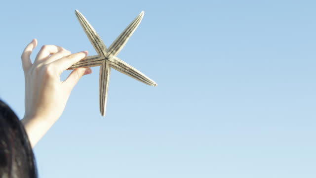 CU Woman holding a starfish up to the sky.