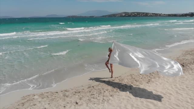 frau hält eine weiße, winken stoff in einem strand - weichheit stock-videos und b-roll-filmmaterial