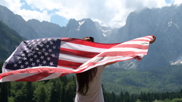 woman holding american flag with a breathtaking view of the mountains - stars and stripes stock videos & royalty-free footage