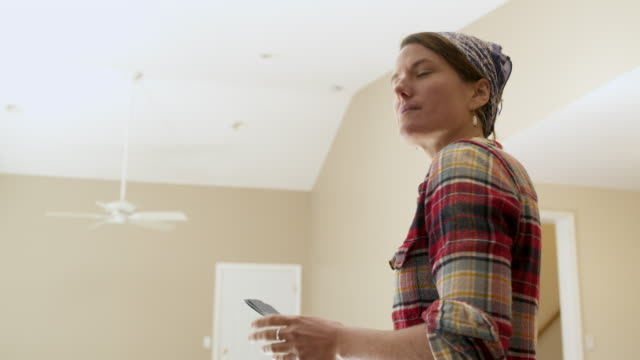 Woman holding and looking at colour swatches in room of new home.