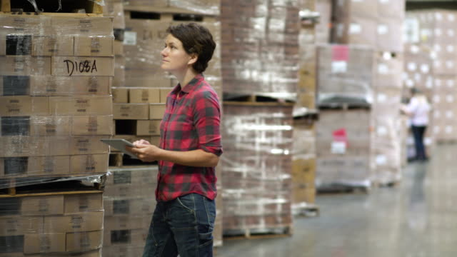 Woman holding and writing on clipboard by stock in warehouse aisle, looking at camera and smiling