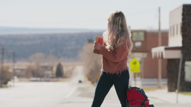 woman holding anywhere sign hitchhiking on remote rural road / loa, utah, united states - ヒッチハイキング点の映像素材/bロール