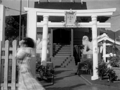 woman holding baby walking out under shinto torii gate tu ms bust of bishop yemyo imamura buddhist 'honpa hongwanji mission hawaii betsuin'... - buddhismus stock-videos und b-roll-filmmaterial