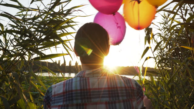 Woman holding balloons at sunset.