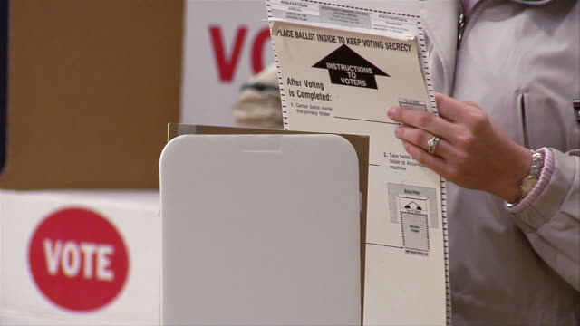 CU, Woman holding ballot into machine, mid section, Ypsilanti, Michigan, USA