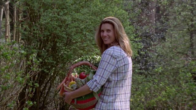 MS R/F Woman holding basket of vegetables in garden / Brussels, Brabant, Belgium