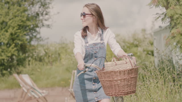 vídeos de stock e filmes b-roll de woman holding bicycle with basket in the summer, looking around - chipping norton england