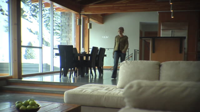 stockvideo's en b-roll-footage met slo mo ws woman holding book walking upstairs, sitting on sofa and reading / whistler, british columbia, canada - bank zitmeubels