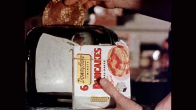 woman holding box that reads 'downey flake pancakes 6' as she places frozen pancakes in toaster / pancakes pop up out of toaster / woman takes... - sirap bildbanksvideor och videomaterial från bakom kulisserna
