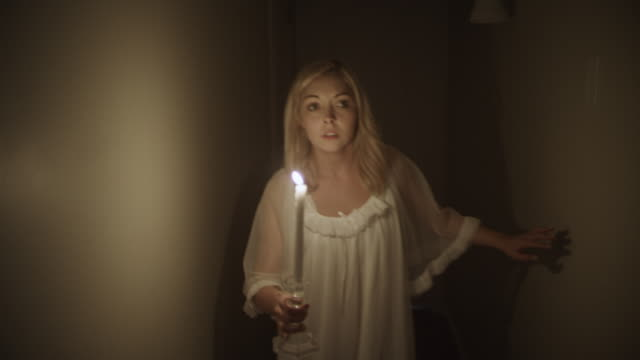 vídeos de stock, filmes e b-roll de woman holding candle in corridor at night surprised by intruder with weapon / springville, utah, united states - câmara de mão