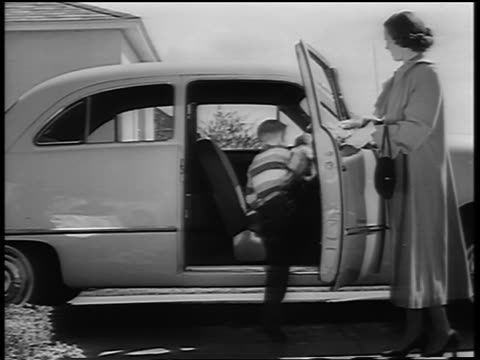 B/W 1950 woman holding car door open for two boys entering / boys start bouncing on seat