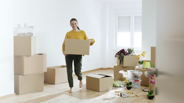 Woman holding cardboard box at her new apartment