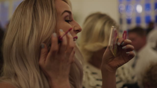 vídeos de stock e filmes b-roll de woman holding cell phone applying lipstick then smiling and laughing / provo, utah, united states - provo