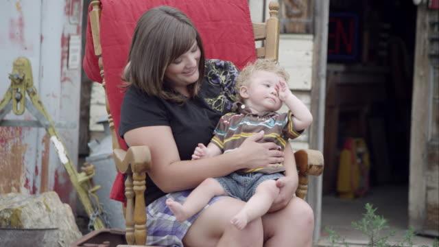 """vídeos y material grabado en eventos de stock de """"woman holding child in lap while rocking in a rocking chair,"""" - en el regazo"""
