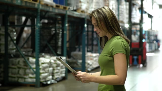woman holding clipboard by aisle of warehouse, forklift machinery in background - pacific islander background stock videos & royalty-free footage