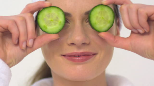 cu slo mo woman holding cucumber in front of eyes / london, greater london, united kingdom - cucumber stock videos & royalty-free footage