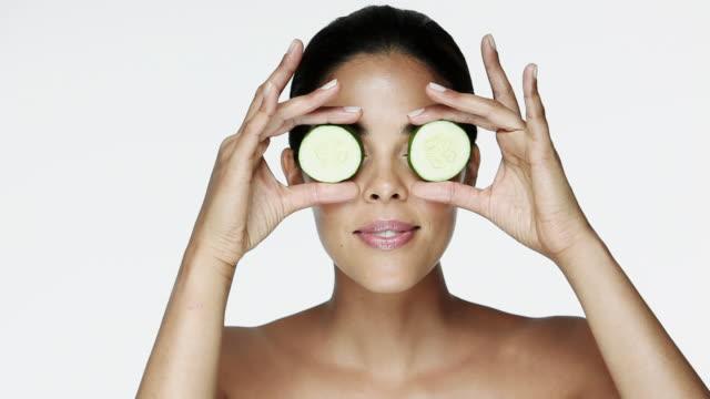 woman holding cucumber slices over eyes - verwöhnen stock-videos und b-roll-filmmaterial