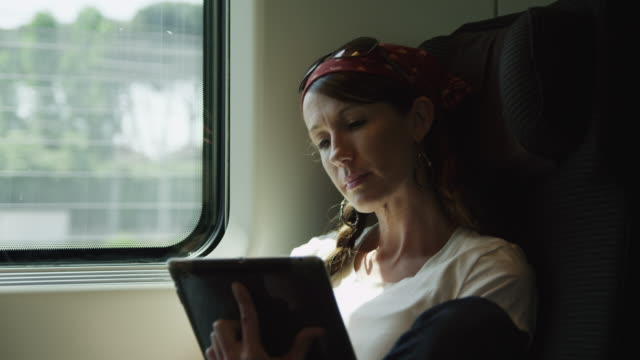 ms woman holding digital tablet sitting on train / italy - casual clothing stock-videos und b-roll-filmmaterial