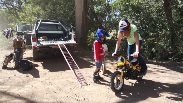 vídeos y material grabado en eventos de stock de a woman holding dirt bike while one young boy is watching her while standing, and the other young boy is on a wooden bike on a sunny summer day - kelly mason videos