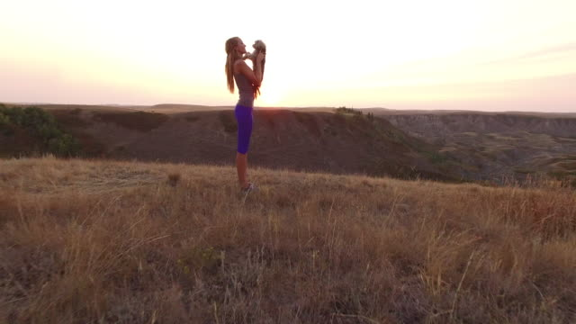 stockvideo's en b-roll-footage met woman holding dog looking out over canyon at sunset - alleen één mid volwassen vrouw
