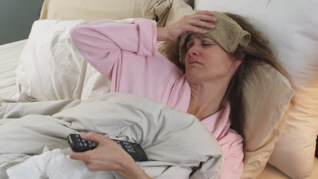 MS Woman holding dump tower against forehead and using TV remote control while lying coughing in bed, Phoenix, Arizona, USA
