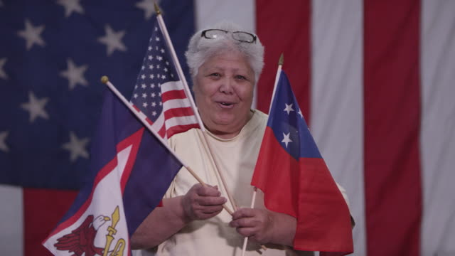 woman holding flag of samoa and american flags - samoa stock videos & royalty-free footage