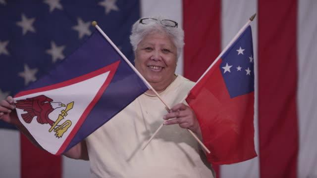 woman holding flag of samoa and american samoa - samoa stock videos & royalty-free footage