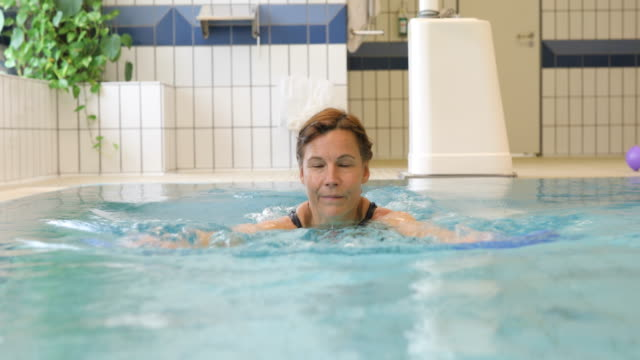 Woman holding floats while exercising in pool