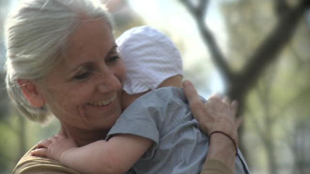 vidéos et rushes de cu woman holding granddaughter (6-11 months), outdoors, new york city, new york, usa - grand mère