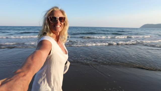 stockvideo's en b-roll-footage met pov van vrouw die hand, loopt langs het strand bij zonsopgang - alleen oudere vrouwen