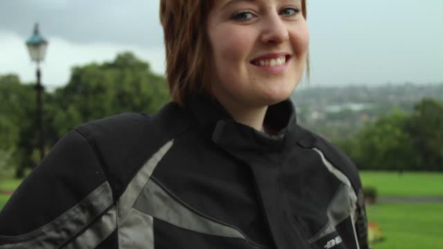 CU LA PAN TU Woman holding helmet under arm, standing by motorcycle in park / London, United Kingdom