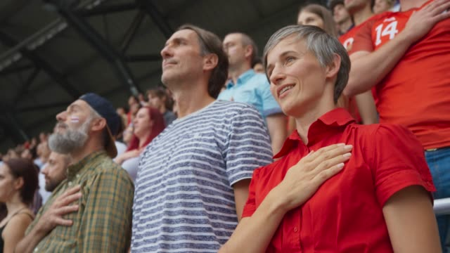 Woman holding her hand over the heart and singing the national anthem on the stadium tribune